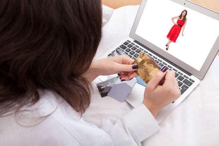 Over the shoulder view of a woman purchasing a dress online with her credit cards photo