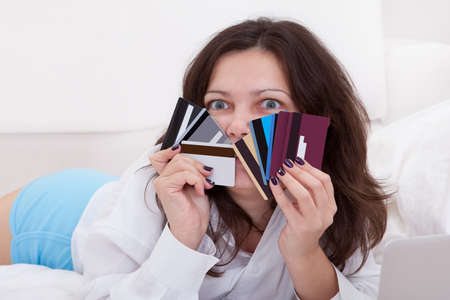 Woman with a fistful of credit cards lying on her bed with her laptop browsing online for something to purchase Stock Photo - 17260804