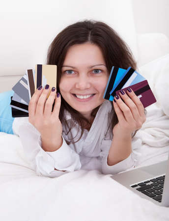 Woman with a fistful of credit cards lying on her bed with her laptop browsing online for something to purchase Stock Photo - 17260803