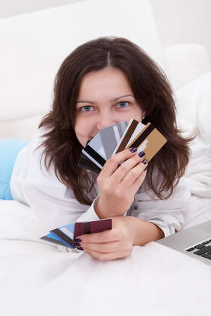 Woman with a fistful of credit cards lying on her bed with her laptop browsing online for something to purchase Stock Photo - 17260797