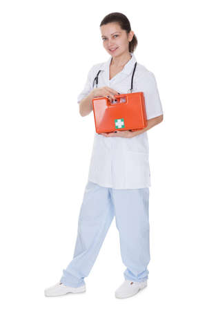 Attractive young smiling female nurse or doctor carrying a portable first aid kit isolated on white photo