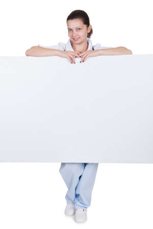 Attractive charming young female doctor or nurse with blank white signboard with copyspace peering around the side as she holds it up Stock Photo - 17260738