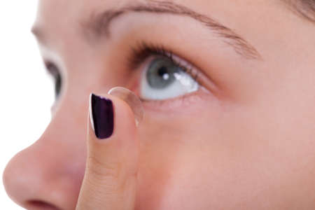 Cropped view of a woman inserting a contact lens into her eye looking upwards in preparation for placing the lens on the cornea Stock Photo - 17260949