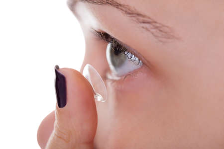 contact lens: Cropped view of a woman inserting a contact lens into her eye looking upwards in preparation for placing the lens on the cornea