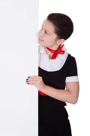 Stewardess holding empty banner. Isolated on white photo