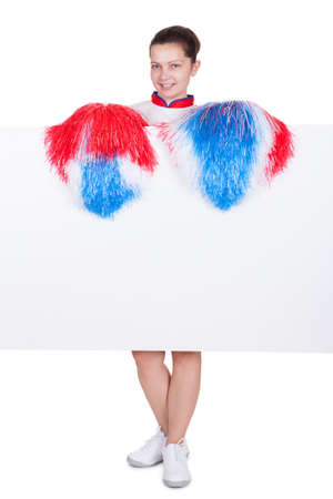 Young attractive female cheerleader holding a blank white sign with copyspace for your text or advertisement with her colorful red photo