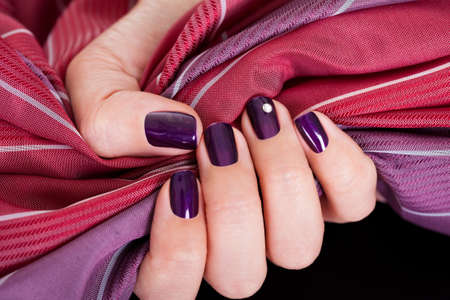 handcare: Woman with beautiful purple nails gripping a color matched maroon and purple fabric to show them off to best advantage