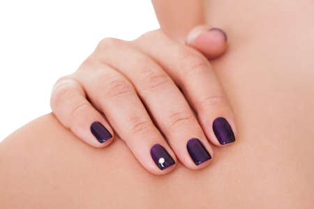 Cropped view image of a woman showing off her beautiful manicured nails with purple nail varnish and a shiny little rhinestone or crystal Stock Photo - 17260857