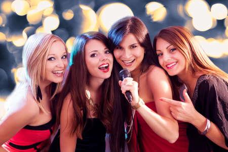 cantando: Cuatro muchachas hermosas elegantes cantando karaoke en el club