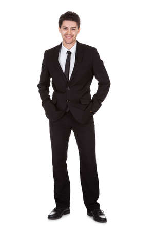 Full length studio portrait on white of a smiling confident young businessman standing with folded arms Stock Photo - 17384674