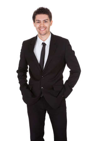 Full length studio portrait on white of a smiling confident young businessman standing with folded arms photo