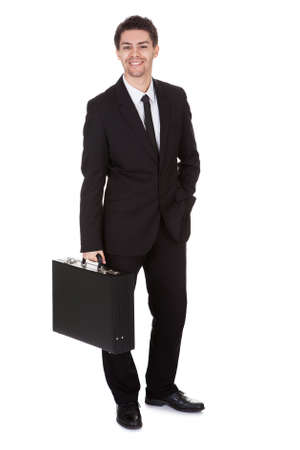 Full length studio portrait on white of a smiling confident young businessman standing with suitcase photo