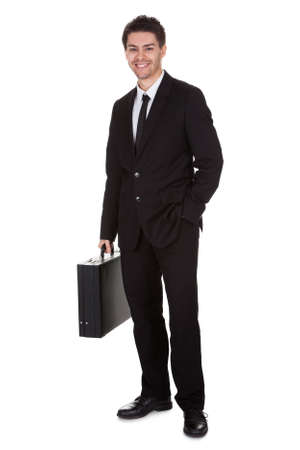 Full length studio portrait on white of a smiling confident young businessman standing with suitcase Stock Photo - 17384687