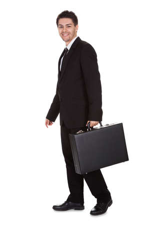 Full length studio portrait on white of a smiling confident young businessman standing with suitcase Stock Photo - 17384680