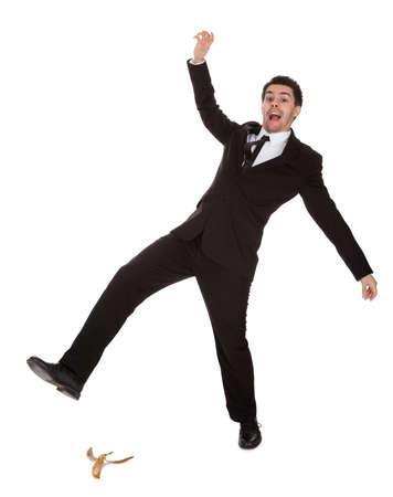 hombre cayendo: Empresario desliz�ndose sobre c�scara de pl�tano. Aislados en blanco Foto de archivo