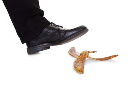 Businessman slipping on banana peel. Isolated on white photo