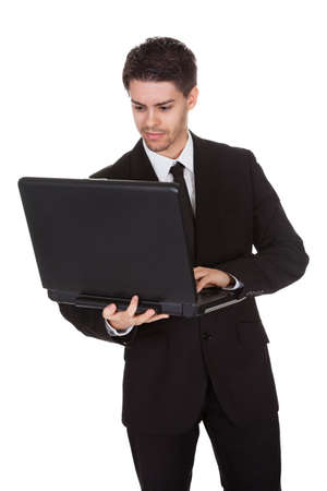 Businessman working on laptop. Isolated on white Stock Photo - 17384558