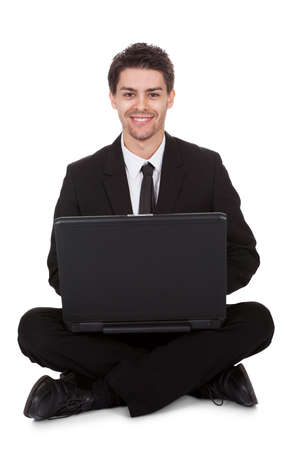 Businessman sitting in yoga pose working on laptop. Isolated on white Stock Photo - 17384668