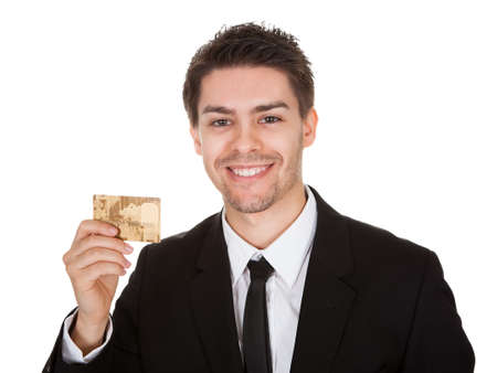 Head and shoulders studio portrait on white of a smiling handsome young businessman holding up a credit card photo