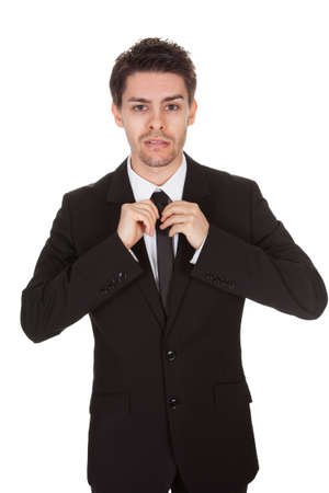 Half body portrait of a handsome young businessman standing straightening his tie isolated on white photo