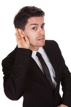 Businessman holding his hand to his ear isolated on white photo