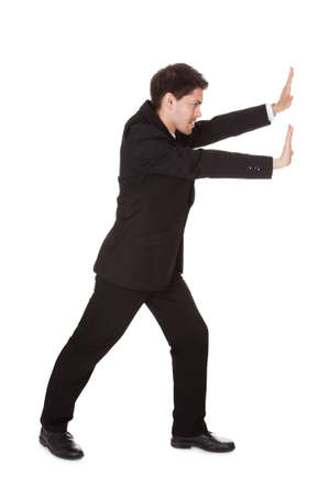 Young man dressed in black is pushing at invisible wall Stock Photo - 17384659