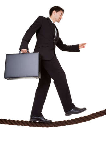 risky innovation: Conceptual image of a businessman carrying a briefcase balancing precariously as he walks a tightrope isolated on white