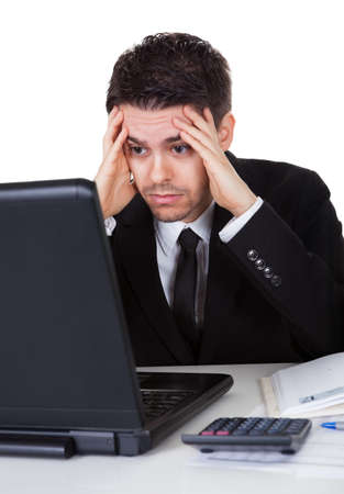 disheartened: Businessman with a look of hopelessness staring at the screen of his laptop with his head resting in his hands