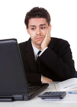 Businessman with a look of hopelessness staring at the screen of his laptop with his head resting in his hands photo