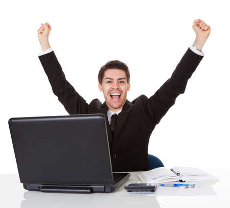 Businessman sitting at his desk rejoicing throwing his arms up in the air and shouting with glee at his success photo