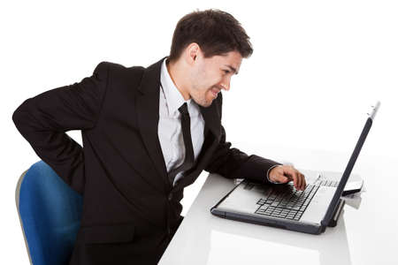 Businessman with lower back ache from sitting with a bad posture in his office chair working on his laptop massaging his back with his hand photo