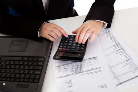 High angle cropped view of the hands of a male accountant doing calculations on a manual calculator while analyzing a report Stock Photo - 17389814
