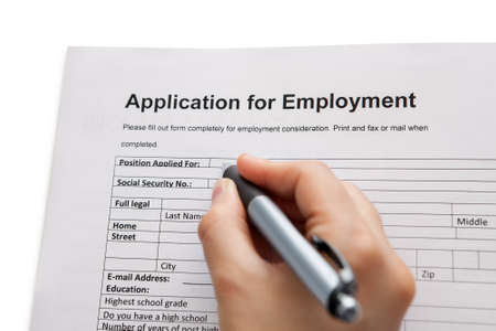 applicant: Closeup of a male hand holding a pen completing a job application form in a career and employment concept Stock Photo