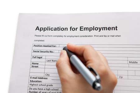 vacante: Primer plano de una mano masculina que sostiene una pluma completando un formulario de solicitud de empleo en un concepto de carrera y empleo