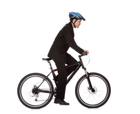 Businessman riding a bicycle to work in his suit exercising for fitness and health and to save on carbon emissions photo