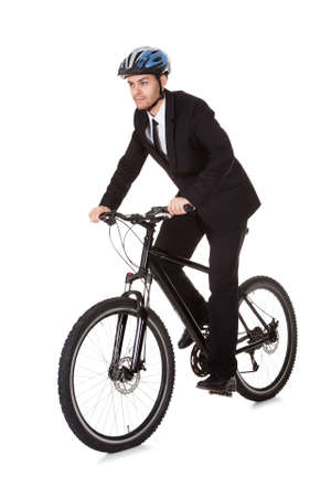 commuting: Businessman riding a bicycle to work in his suit exercising for fitness and health and to save on carbon emissions Stock Photo