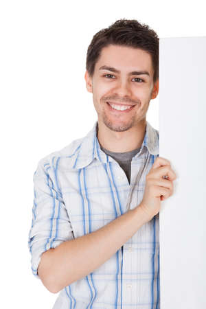 Smiling casual handsome young man holding up a blank white sign in front of his chest with copyspace for your text photo