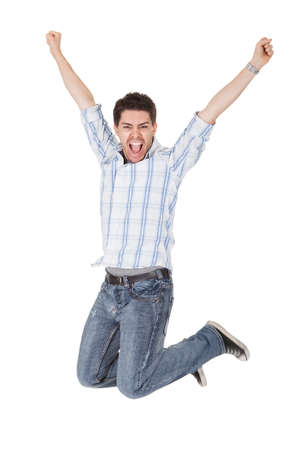 Casual handsome young man in jeans shouting for joy raising his hands above his head photo