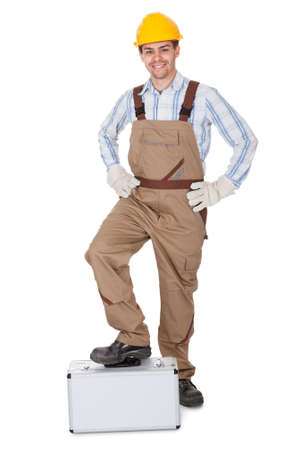 Full body portrait of a smiling young workman or repairman in dungarees and a hardhat carrying a toolkit isolated on white photo