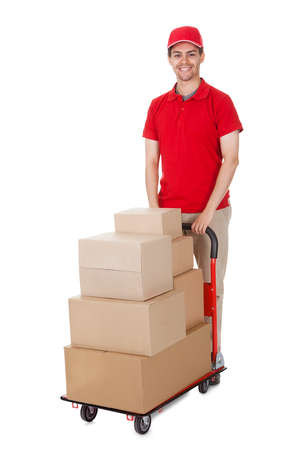 hand truck: Cheerful young deliveryman in a red uniform holding trolley loaded with cardboard boxes isolated on white