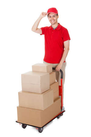 Cheerful young deliveryman in a red uniform holding trolley loaded with cardboard boxes isolated on white photo