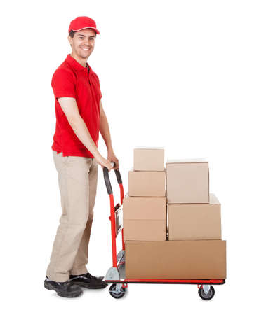 pushing: Cheerful young deliveryman in a red uniform holding trolley loaded with cardboard boxes isolated on white
