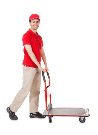 Cheerful young deliveryman in a red uniform holding trolley loaded with cardboard boxes isolated on white Stock Photo - 17384673