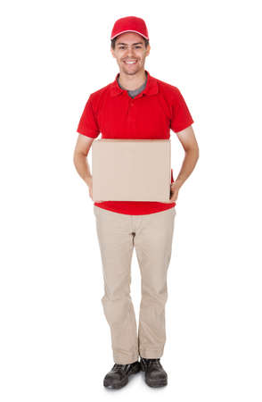 Smiling male courier in a red shirt and cap delivering a parcel in a brown cardboard box Stock Photo - 17384690