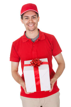 deliveryman: Cheerful smiling young male messenger delivering a decorative gift isolated on white