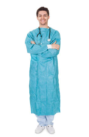 hospital gown: Smiling confident young surgeon wearing a gown and stethoscope standing with his arms crossed isolated on white