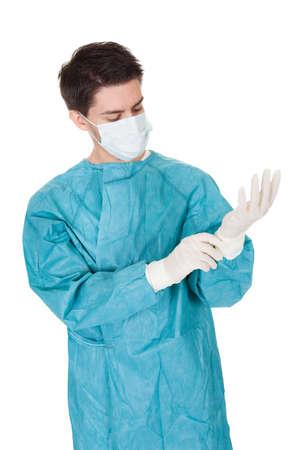 operation gown: Cirujano masculino joven con una m�scara y un vestido de ponerse guantes quir�rgicos desechables antes de ir al teatro aislado en blanco