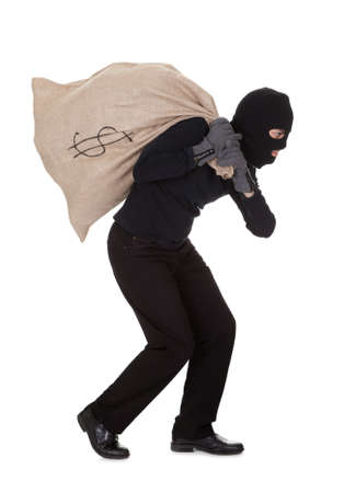 larceny: Thief in black clothes wearing a balaclava carrying a large bag of money with a dollar sign over his shoulder isolated on white