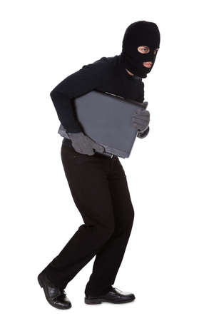 Thief dressed in black and wearing a balaclava stealing a laptop computer and making a furtive escape isolated on white photo