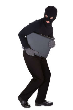 Thief dressed in black and wearing a balaclava stealing a laptop computer and making a furtive escape isolated on white Stock Photo